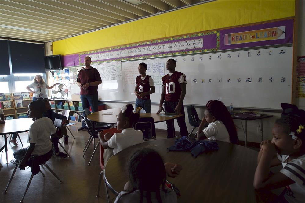 (R to L) Terrell Jones, D'Shawn McGlown and Coach Eric Valentine read to second graders at Windsor
